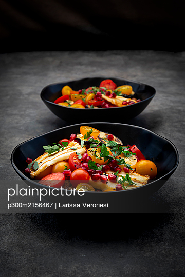 Bowls of Persian salad with tomatoes, grilledhalloumicheese, eggplant, pomegranate seeds, sumac, black sesame and parsley - p300m2156467 by Larissa Veronesi