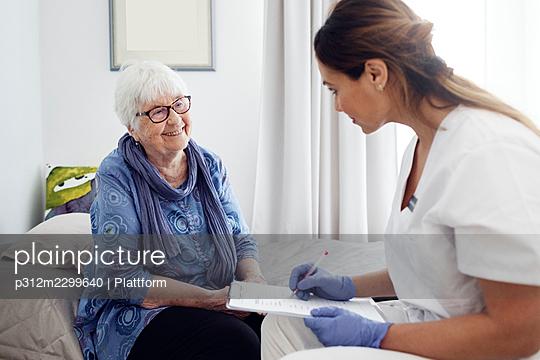 Nurse with elderly woman at home - p312m2299640 by Plattform