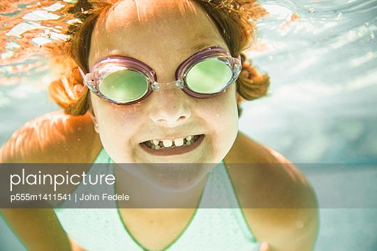 Caucasian girl swimming underwater in swimming pool - p555m1411541 by John Fedele