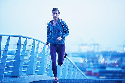 Female runner running on urban footbridge at dawn - p1023m1201833 by Ryan Lees