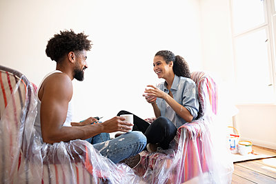 DIY Couple talking and drinking coffee, taking a break from painting - p1192m2016740 by Hero Images