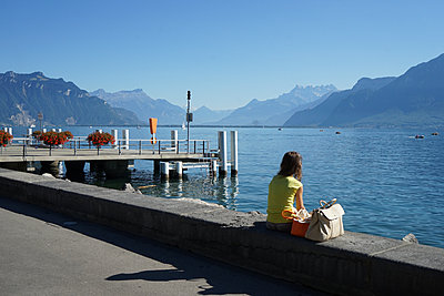 A woman sitting by Geneva's lake - p1610m2208689 by myriam tirler