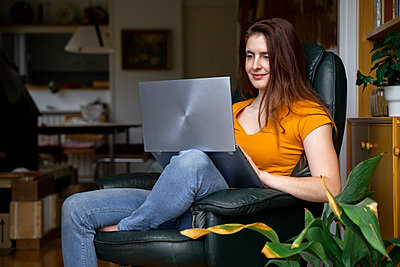 Beautiful woman using laptop while sitting on chair at home - p300m2264512 by VITTA GALLERY