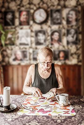Senior man eating breakfast - p312m1113873f by Caluvafoto