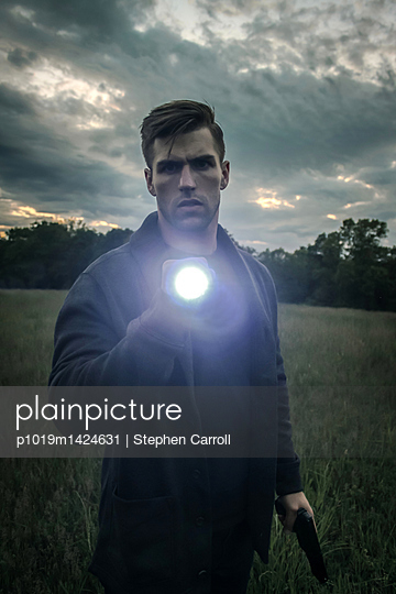 Man with flashlight and pistol - p1019m1424631 by Stephen Carroll