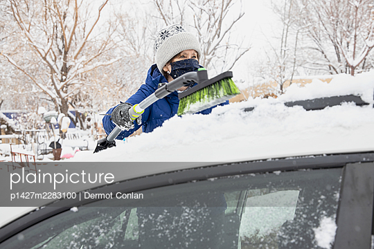 USA, New Mexico, Santa Fe, Woman in face mask removing snow from car - p1427m2283100 by Dermot Conlan