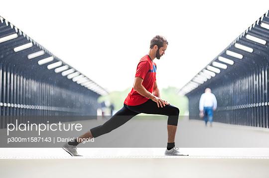 Man stetching on a bridge - p300m1587143 von Daniel Ingold