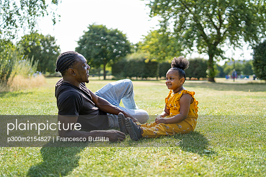 Father and daughter relaxing on a meadow in a park - p300m2154827 by Francesco Buttitta