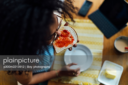 Close-up of young woman with curly hair eating bread at table - p300m2213912 by Boy photography