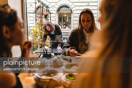 Multi-ethnic female friends having food in restaurant while waiter cleaning table outside - p426m2279773 by Maskot