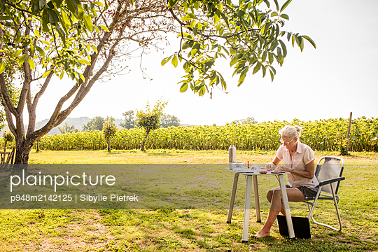 Woman sitting at the camping table and writing - p948m2142125 by Sibylle Pietrek