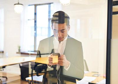 Asiatischer Mann mit Smartphone im Büro - p1124m1181502 von Willing-Holtz