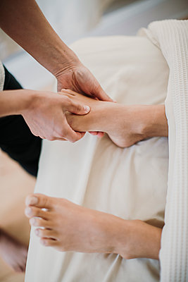 A massage therapist massages her client's right foot - p1166m2107020 by Cavan Images