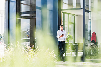 Businessman outside office building looking at cell phone - p300m1505703 by Uwe Umstätter