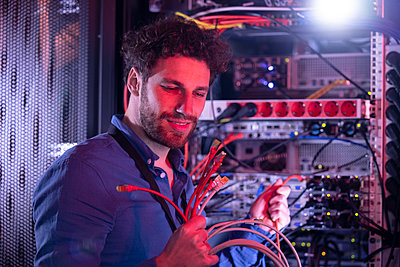 Male IT technician looking at patch cord cables while standing by server rack - p300m2275202 by Florian Küttler