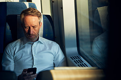 Man using cell phone in train - p312m2208171 by Johan Alp