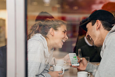 View of happy young couple using smart phone in cafe through glass - p426m1003791f by Maskot