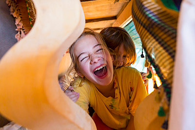 Caucasian brother and sister laughing under table - p555m1522792 by Marc Romanelli