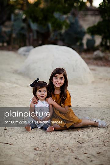 Sisters Posing for Camera in Desert Garden in San Diego - p1166m2292781 by Cavan Images