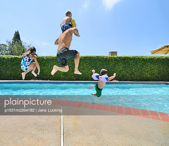 Father And Children Jumping Into Pool - p1531m2264182 by Jens Lucking