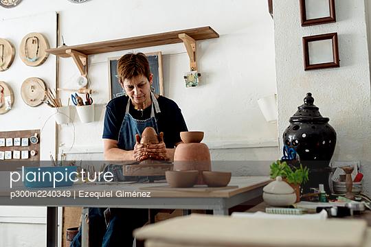 Valencia, Spain. Woman working in a ceramic workshop making clay sculpture on the lathe. - p300m2240349 von Ezequiel Giménez