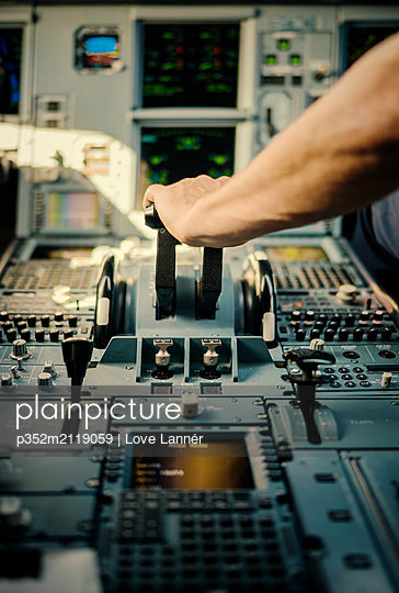 Pilot´s hand on airplane control panel - p352m2119059 by Love Lannér