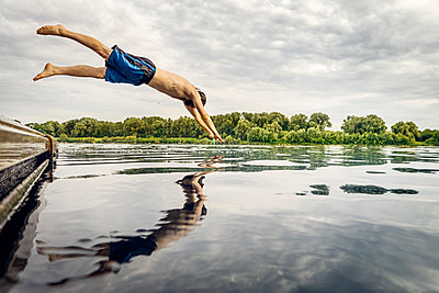 Man jumping from jetty into water - p300m1192090 by Matthias Buchholz