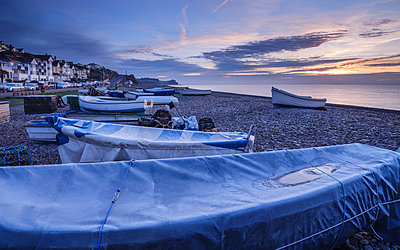 Serene dawn scene of fishing boats on the pebbled beach at Budleigh Salterton, Devon, England, United Kingdom - p871m2111482 by Baxter Bradford