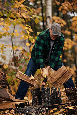 Mature man splitting logs in autumn forest, Upstate New York, USA - p924m1404260 by heshphoto