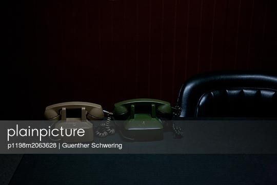 Zwei Telefone vor Ledersessel - p1198m2063628 von Guenther Schwering