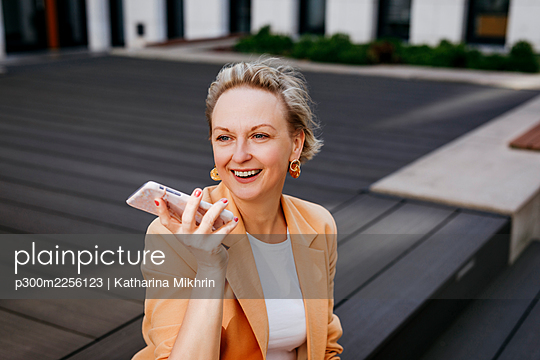 Happy female entrepreneur talking through smart phone while sitting on floorboard - p300m2256123 by Katharina Mikhrin