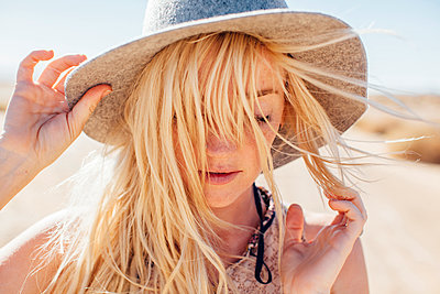 Close-up of woman in sun hat enjoying vacation at desert on sunny day - p1166m1227799 by Cavan Images