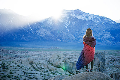 Rear view of woman wrapped in blanket looking at Alabama Hills - p1166m1473995 by Cavan Images