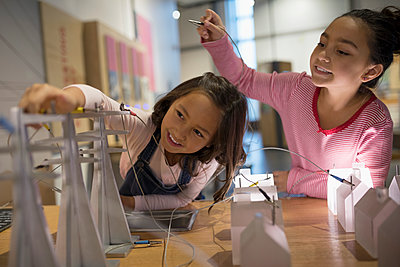 Sisters playing with electricity grid exhibit in science center - p1192m1194237 by Hero Images