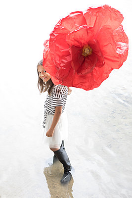 Portrait of smiling girl standing in a lake with oversized red artificial flower - p300m2062249 von Petra Stockhausen