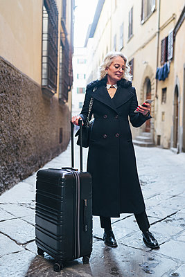 Mature businesswoman wearing black coat standing in an alley with rolling suitcase looking at cell phone - p300m2102997 by Francesco Buttitta