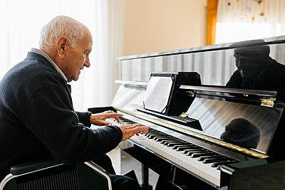Senior man sitting in wheelchair playing piano at home - p300m2160580 von Josep Rovirosa