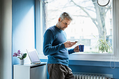 Mature man standing with coffee mug standing in living room looking at smartphone - p300m2180417 by 27exp