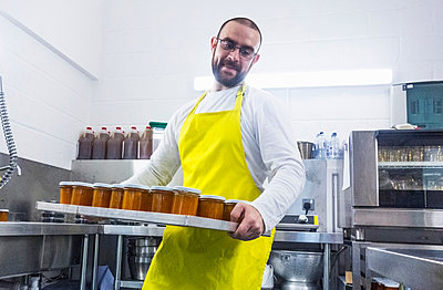Man carrying tray of fresh jam in industrial kitchen - p429m2023256 by Seb Oliver