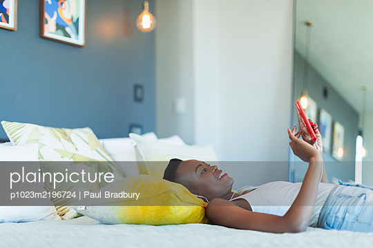 Young woman relaxing on bed, listening to music with headphones and mp3 player - p1023m2196724 by Paul Bradbury