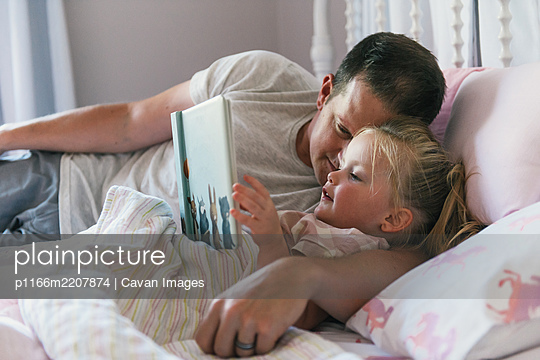 Father snuggling with toddler daughter as she reads bedtime story book - p1166m2207874 by Cavan Images