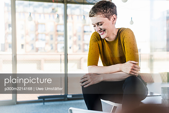 Happy businesswoman sitting on desk in office - p300m2214168 by Uwe Umstätter
