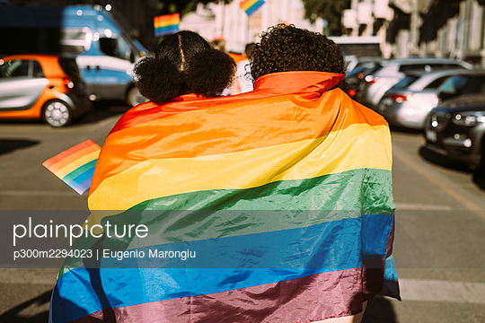 Female friends wrapped in rainbow flag on sunny day - p300m2294023 by Eugenio Marongiu