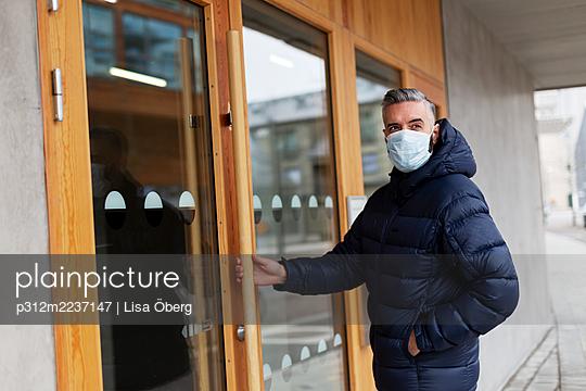 Man wearing face mask opening door - p312m2237147 by Lisa Öberg