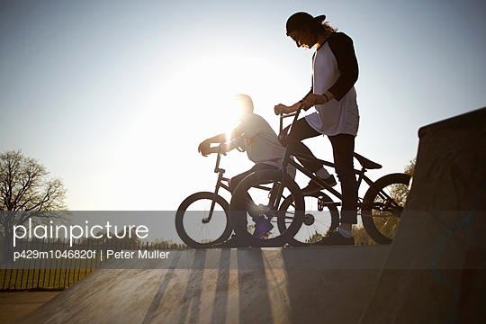 Two young men on bmx bikes at skatepark