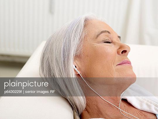 Aeltere Frau hoert Musik mit mp3-Player  - p6430229f von senior images RF
