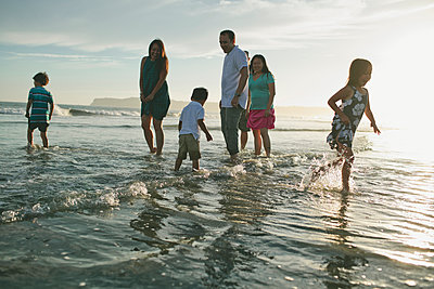 Family enjoying in sea against sky during sunset - p1166m1182827 by Cavan Images
