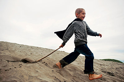 Playful boy with stick walking on sand at beach against sky - p1166m1415126 by Cavan Images