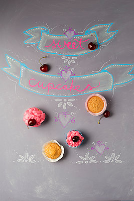 Cup cakes with cherry topping on painted blackboard - p300m1469994 by Mandy Reschke