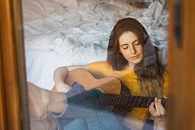 Portrait of relaxed young woman sitting behind windowpane playing guitar - p300m1581643 by Kike Arnaiz